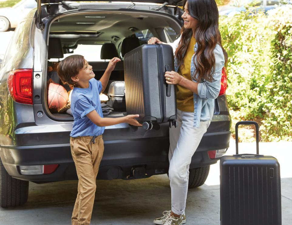 A mom and her child lifting a heavy suitcase out of the trunk of an SUV